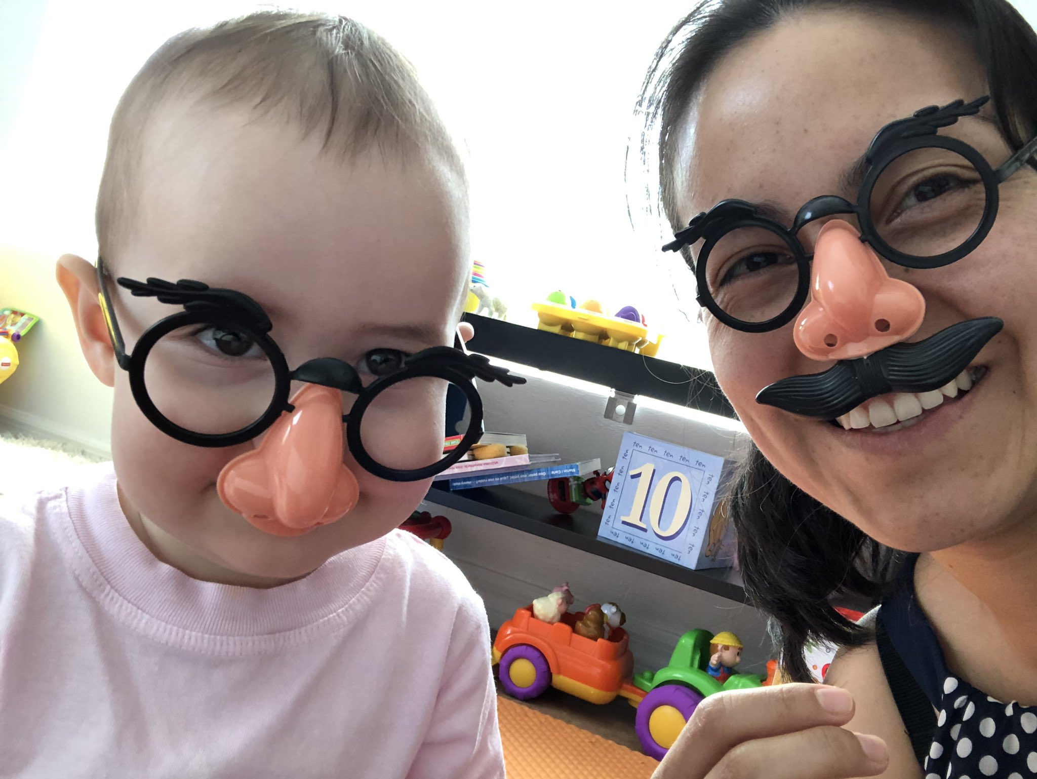 Yeni and AnneMarie wearing a fake nose and glasses.